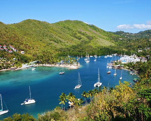 A beach with boats at Oasis Marigot surrounded by wooded area.