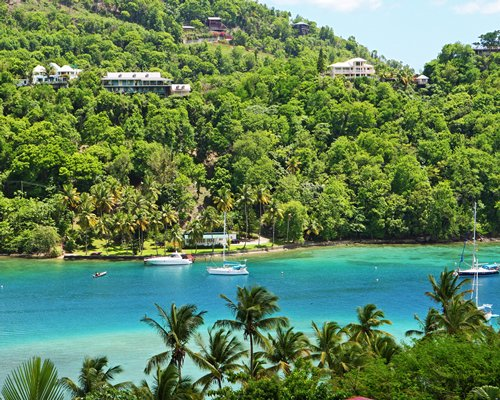 A beach with floating boats alongside the Oasis Marigot resort surrounded by wooded area.