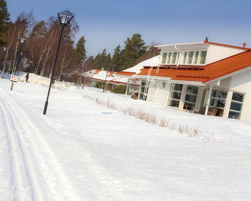 An exterior view of the Holiday Club Katinkulta resort covered in snow.