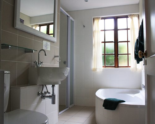A bathroom with a single sink vanity and a bathtub.