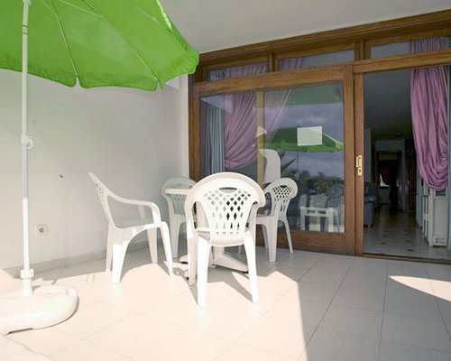 Outdoor patio with patio chairs and sunshade.