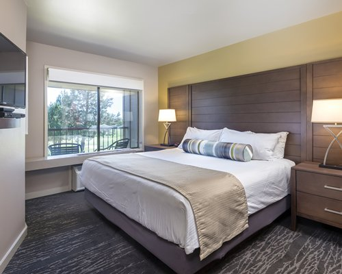 A well furnished bedroom with a queen bed and outdoor patio.