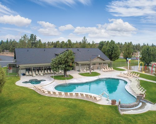 An aerial view of the outdoor swimming pool and kiddie pool with chaise lounge chairs alongside the resort unit.