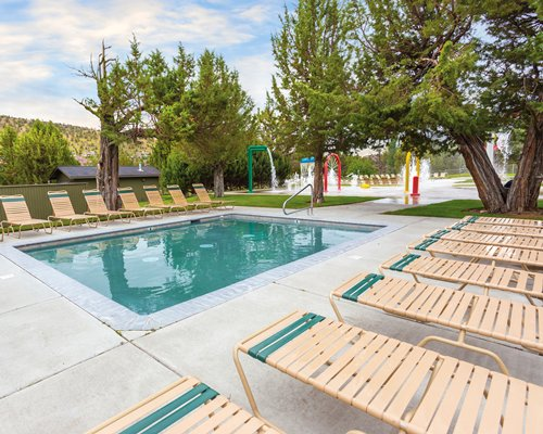 An outdoor swimming pool with chaise lounge chairs.