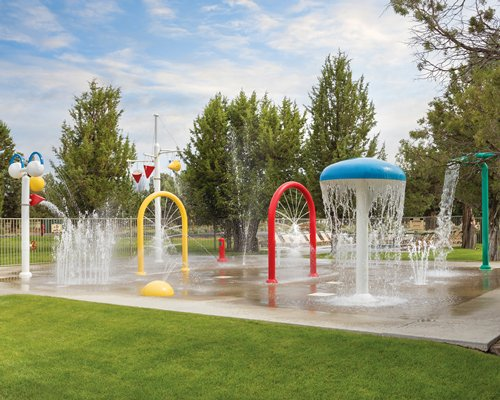 A water themed outdoor play area with a raining mushroom umbrella.