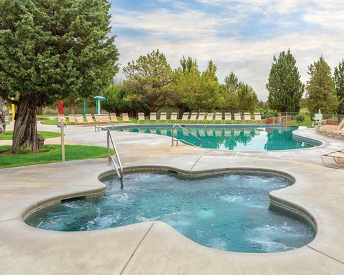 A scenic outdoor swimming pool and hot tub with chaise lounge chairs.