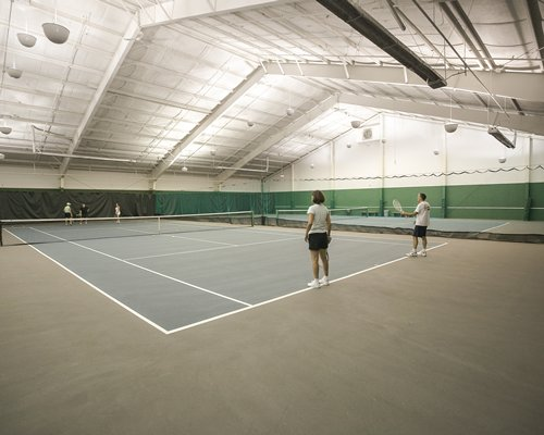 People playing tennis at an indoor tennis court.