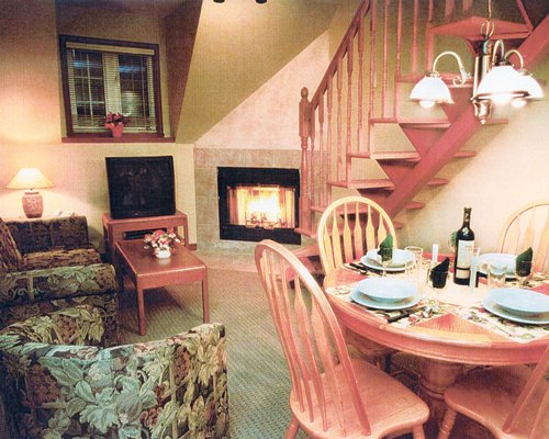 A well furnished living room with a television dining area stairway and fire in the fireplace.