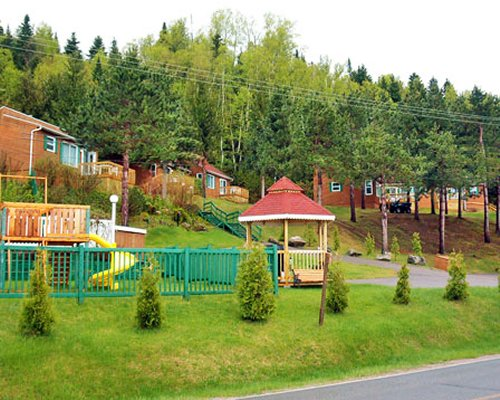 Outdoor kids playscape surrounded by wooded area.