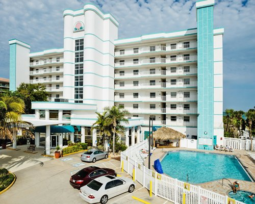 An exterior view of resort condo with parking lot alongside the swimming pool.