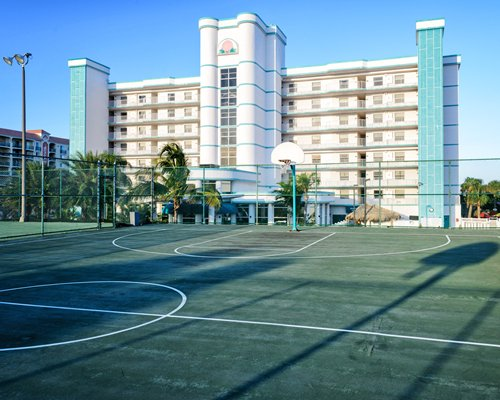 An outdoor basketball court alongside multi story resort units.
