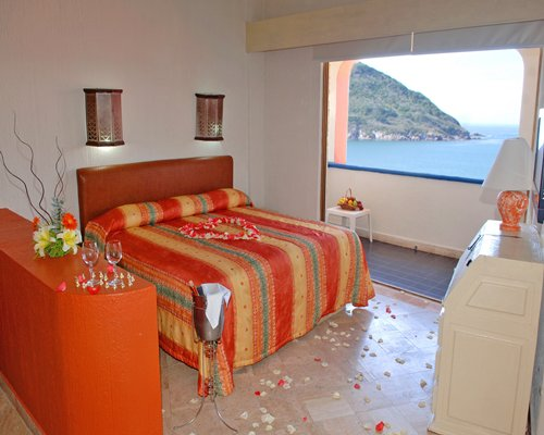 A well furnished and decorated bedroom with a king bed and ocean view.