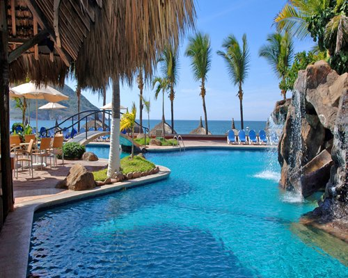 Outdoor large grotto pool with chaise lounge chairs bridge palm trees and sunshades.