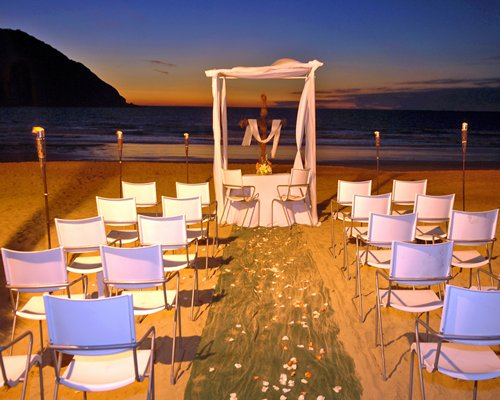 A beach wedding set up alongside the ocean at dusk.