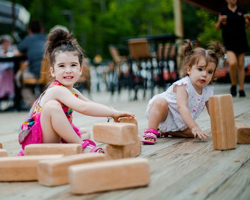 View of kids playing with bricks at an outdoor dining.
