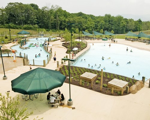 An aerial view of large outdoor swimming pool kiddie pool and dining with sunshade alongside wooded area.