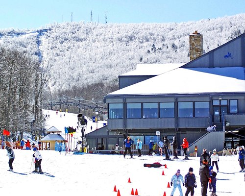 Group of people skiing in front of a resort condo covered in snow.