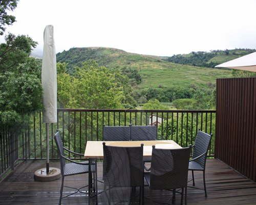A balcony with a dining table with the view of hills.