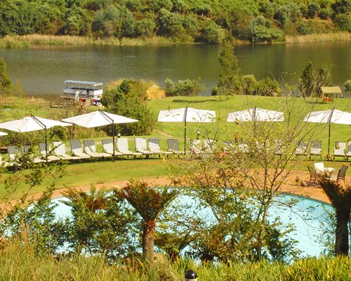 An outdoor swimming pool with chaise lounge chairs alongside the lake and wooded area.