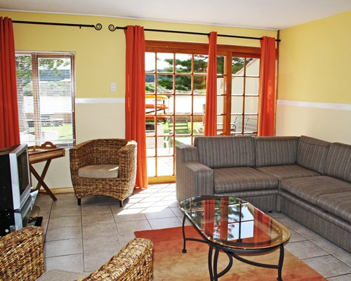 A well furnished living room with sofas television and an outside view.
