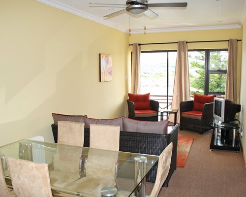 A well furnished living room with a television glass top dining area and outdoor view.