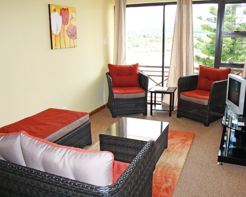 A well furnished living room with a television and outside view.