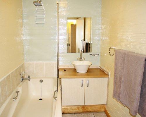 A bathroom with a shower bathtub and single sink vanity.