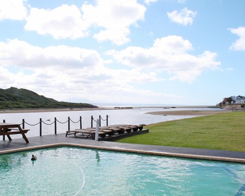 An outdoor swimming pool with chaise lounge chairs with the waterfront.