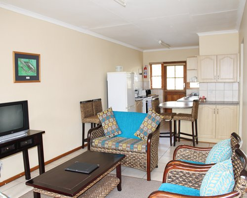 A well furnished living room with a television open plan kitchen a breakfast bar.