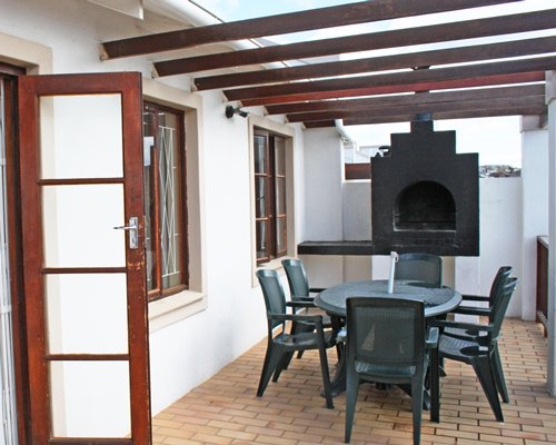 A view of patio furniture on the balcony with a gas log fireplace.
