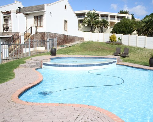 An outdoor swimming pool with hot tub alongside resort units with private balconies.