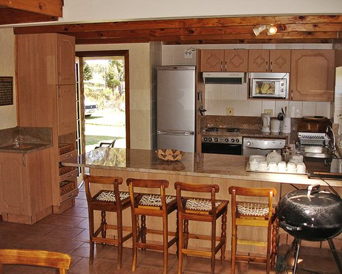 A well equipped kitchen with a breakfast bar barbecue grill and patio.