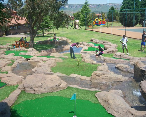 An outdoor picnic area with a putt putt golf course alongside a tennis court.