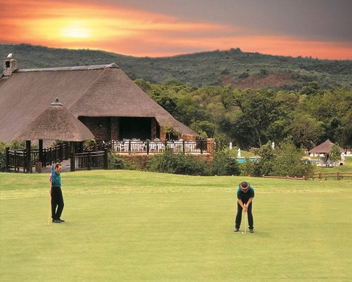 View of Kruger Park Lodge with golfers playing golf at the golf course.