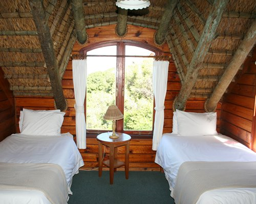 A well furnished attic bedroom with two twin beds and an outside view.