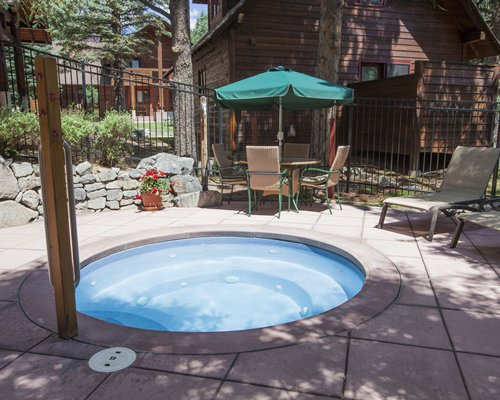 An outdoor hot tub with patio furniture alongside resort units.