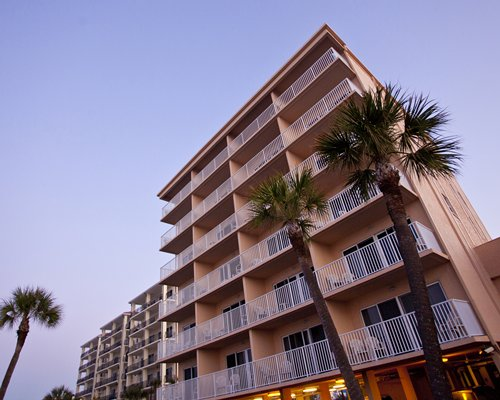 A ground view of the multi story condo with palm trees.