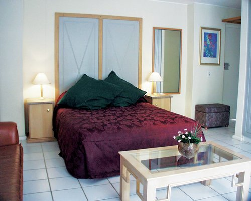 A well furnished bedroom with double bed and two lamps.