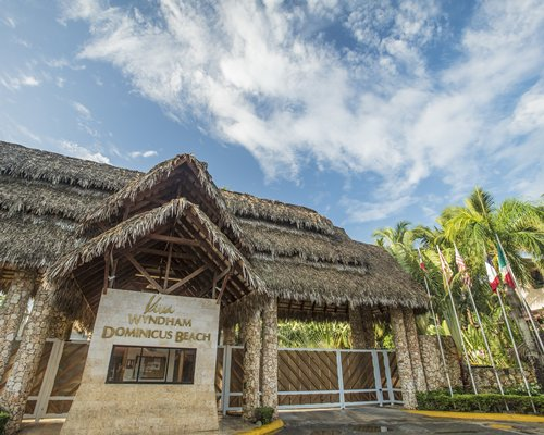 Exterior view of a thatched covered unit at Viva Vacation Club surrounded by palm trees.