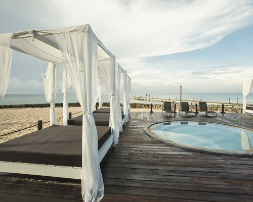 Outdoor hot tub with beach beds and chaise lounge chairs alongside the beach with a pier.