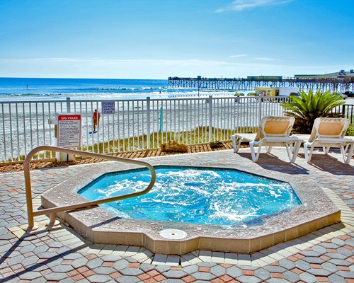 Outdoor hot tub with chaise lounge chairs alongside the beach with a pier.