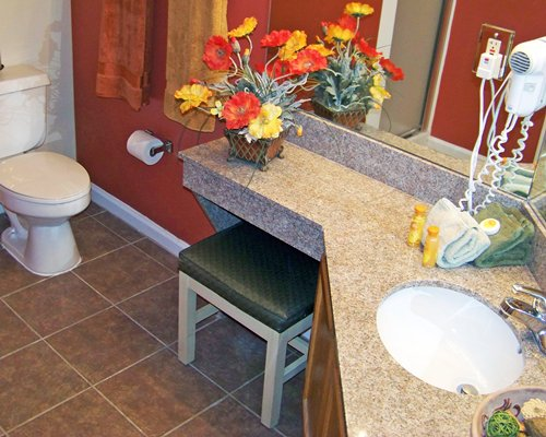 A bathroom with a sink and chair.