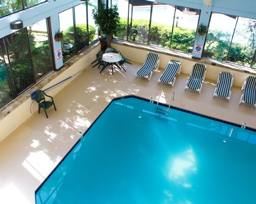 Indoor swimming pool with chaise lounge chairs patio furniture and outside view.