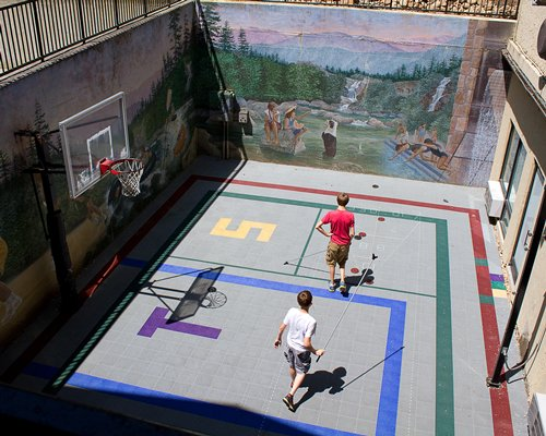 Two kids playing in a basketball court.
