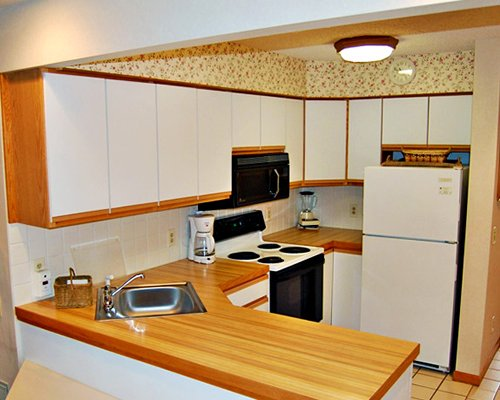 A well equipped kitchen with a microwave oven and a refrigerator.