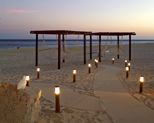 Pathway to a dining area alongside beach at dusk.