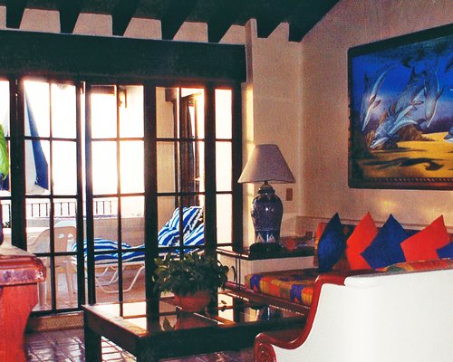 A well furnished living room alongside a balcony with chaise lounge chair.