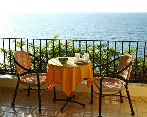 A balcony with patio furniture alongside the ocean.