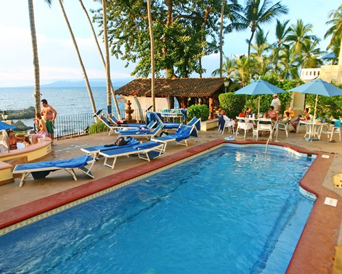 An outdoor swimming pool with hot tub chaise lounge chairs alongside the ocean.