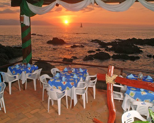 A fine dining area alongside the ocean at dusk.